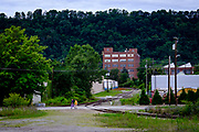 """Two women cross railroad tracks in the town of New Kensington, Pa.<br /> <br /> New Kensington, a small city located twenty miles northeast of Pittsburgh, is known as the """"Birthplace of the Aluminum Industry"""" since it was where the Aluminum Company of America's (ALCOA) first facility was built in 1891. ALCOA presence drove the area's economy for over sixty years.<br /> <br /> When ALCOA closed its New Kensington operations in 1971, 3,300 jobs were lost – a fifth of the local population. As a result,  property values rapidly declined and many homeowners became underwater on their mortgages.<br /> <br /> The population shrank nearly in half, from 26,000 in the early 1970s to about 14,000. Businesses moved to malls or suburban commercial strips and the buildings that previously housed them fell into decay and the city's tax revenues plummeted."""
