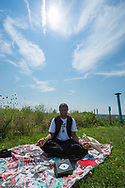 """Merrick, New York, USA. August 21, 2017. DAVID KENT, from Freeport, NY, sits meditating in a lotus pose with his back to the Partial Solar Eclipse and eyes shut, on the hilltop of Norman J Levy Park and Preserve. Kent said, """"I do meditation to help align myself with the spiritual energy coming from the eclipse.""""  The partially eclipsed sun is at center of top, to right of two contrails in the sky. The solar eclipse was 70% at maximum point, and Levy Park is the highest point of the South Shore of Long Island. Kent has his shoes and a Kenzo World box with a big eye on his blanket."""