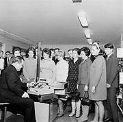 Man demonstrating use of modern cash register till watched by shop staff, Helsinki, Finland, 1960s