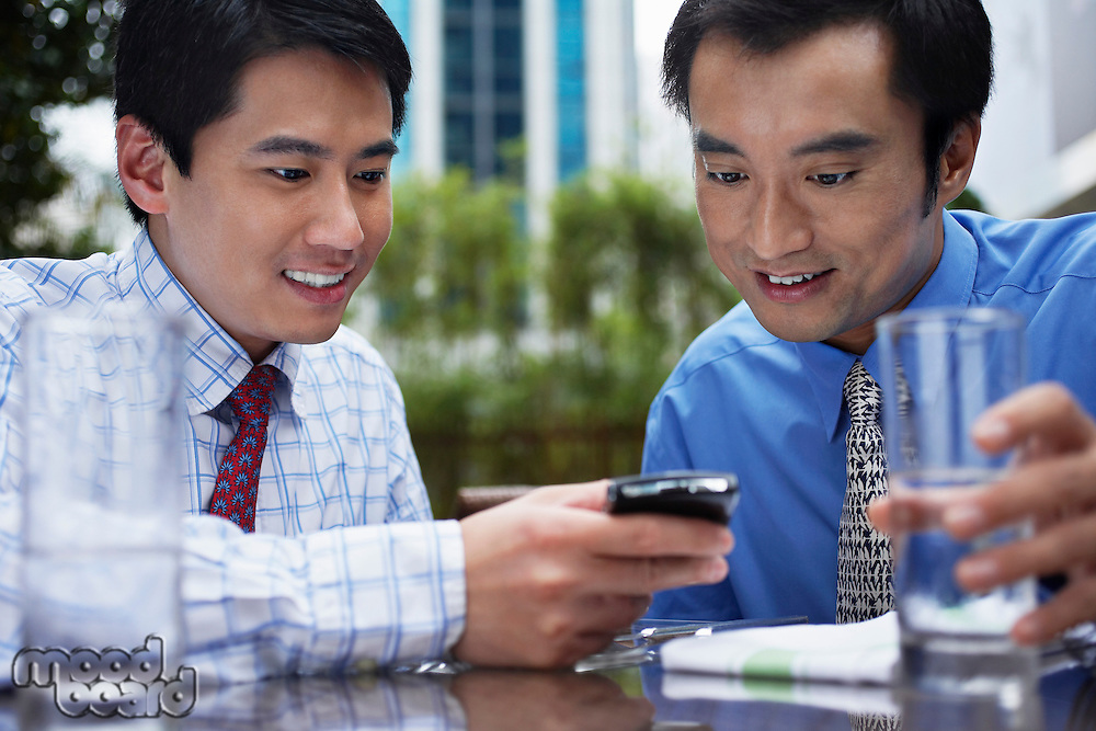 Two business man using mobile phone sitting in outdoor cafe