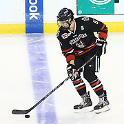 Matt Benning #5 of the Northeastern Huskies with the puck during The Beanpot Championship Game at TD Garden on February 10, 2014 in Boston, Massachusetts. (Photo by Elan Kawesch)