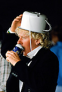 Racegoer with chamber pot on his head drinking can of Foster's Lager at Melbourne Cup Races at Victoria Racing Club, Australia