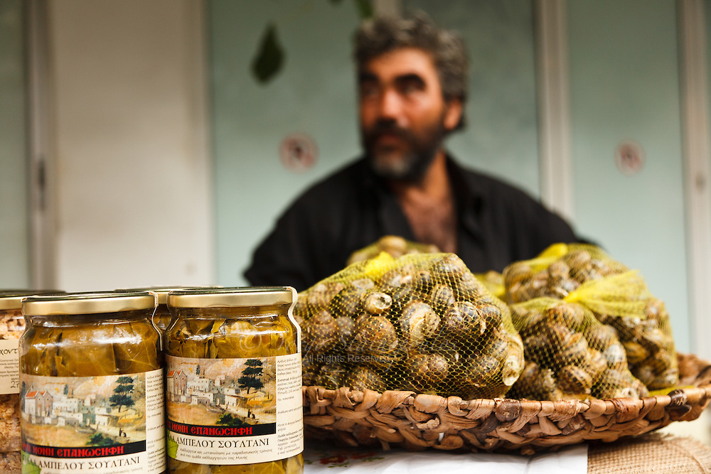 Hohlious (snails) and dolmades (stuffed grape leaves) are the delicacies that this  man sells at the local market in the village of Houdetsi, Crete Greece.