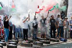 © Licensed to London News Pictures. 06/07/2017. Shenstone, Staffordshire, UK. Activists let off the colours of Palestine flag smoke flares and have a minutes silence around coffins representing dead children of Palestine murdered by Israeli UAV weapons. On the second anniversary of Israel's brutal assault on Gaza in July 2014  in which 2,200 Palestinians were killed, including more than 550 children, campaigners from across the UK travel to Elbit's factory in Shenstone, Lichfield in Staffordshire for a non-violent picket outside the factory gates to demand that the UK stops arming Israel and that Elbit's factory ceases their production of death drones. Elbit's death drones are used by The Israel Defence Force against the people of Palestine. Photo credit: Graham M. Lawrence/LNP