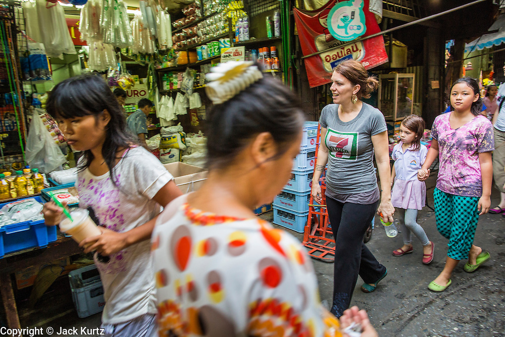 01 APRIL 2013 - BANGKOK, THAILAND:  Amy Hupe (CENTER) and her daughter, Elijah Hupe, and their friend, Amita Thapa, walk through a Bangkok market on their way to dinner.    PHOTO BY JACK KURTZ