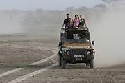 Africa, Tanzania, Serengeti National Park, Safari tourists in an open top Jeep