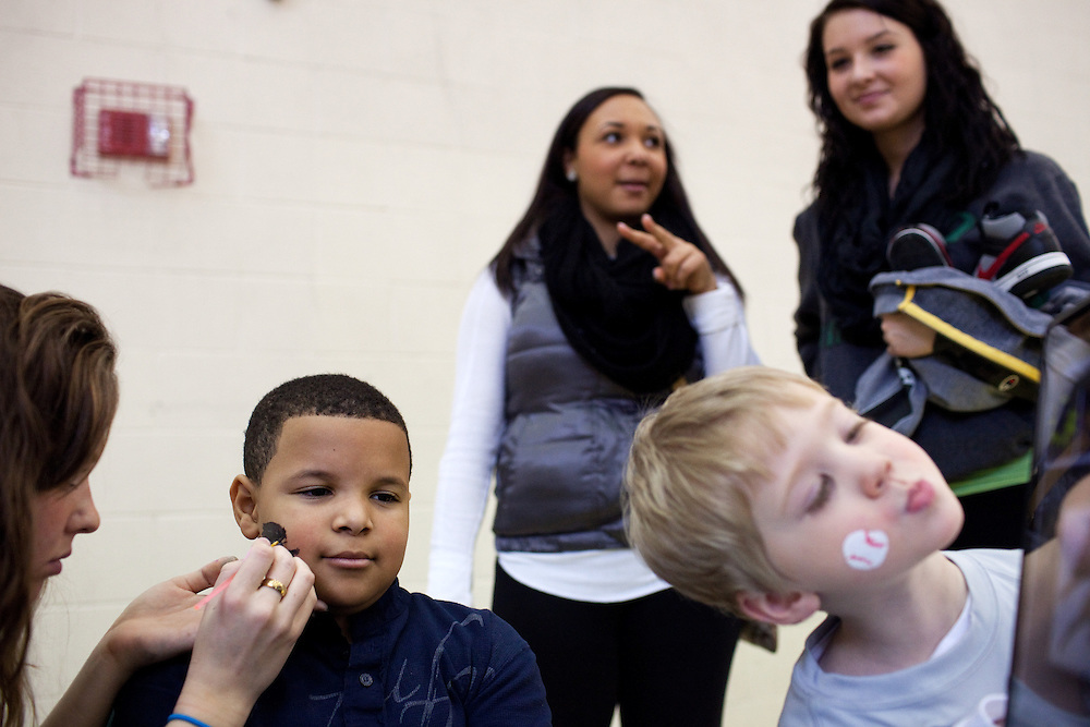 Students Lauren Mckee (upper left) and Camerons Kinnen's younger brothers, Kalon Jackson (left) and Cameron Kinnen, get their faces painted by Katie Eastman. The Ohio University Ping Center hosted the Sibs Bash during Sibs Weekend in Athens, Ohio on Saturday, February 9, 2013. Photo by Chris Franz