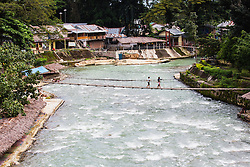 A foot bridge crosses the Bahorok River in the village of Bukit Lawang in northern Sumatra, Sumatra, Indonesia