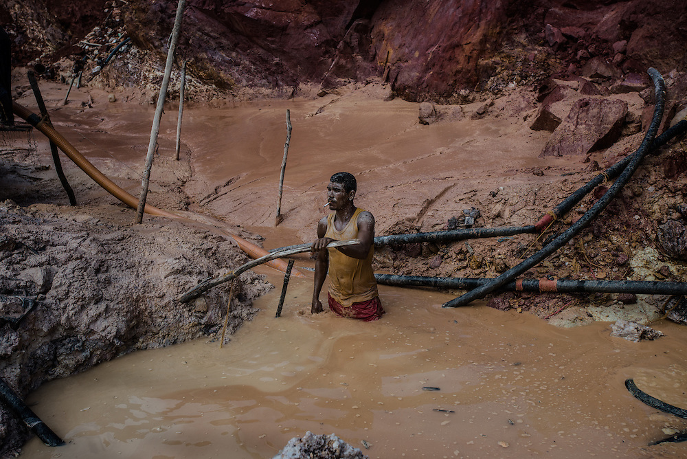 """LAS CLARITAS, VENEZUELA - JULY 20, 2016:  Thousands of Venezuelans are flocking to illegal gold mines, like this one, called """"Cuatro Muertos"""" (""""Four Dead"""" because four miners have died here since the mine was dug) in hopes of surviving the current economic crisis by earning in gold instead of the national currency, whose value steadily falls due to the world's highest inflation.  From this remote part of the jungle the migrant miners have become the vectors of a new epidemic of malaria, because the hot, swampy conditions of the mines make for an ideal breeding ground for mosquitos. Miners spread the disease as they return home with earnings or pay visits to family members. Dozens of miners that work in this mine said that they have contracted malaria multiple times, some even dozens of times. The economic crisis has also left the government without the financial resources to control the disease - they are unable to fumigate homes, provide medicines to everyone that is sick, or even to test all patients with symptoms of malaria in many places. PHOTO: Meridith Kohut for The New York Times"""