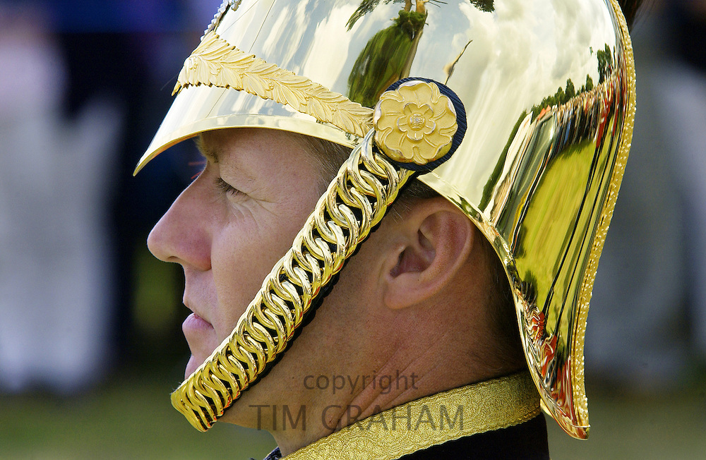 Man wears a brass helmet with chain chin strap, England
