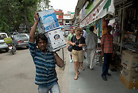 Man working with foreigners in the background /street scene in Delhi, India.