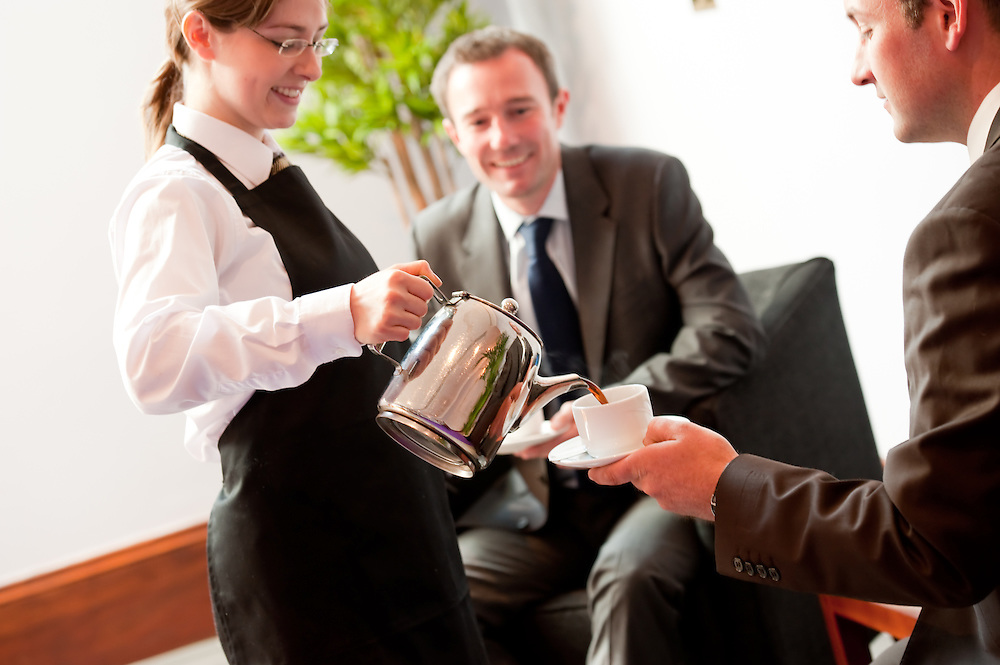 Waitress pouring coffee for two smiling business men in suits