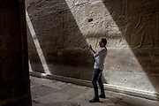n Egyptian tourist take photos under sunlit hieroglyphs in the dark recesses of the ancient Egyptian Luxor Temple, Nile Valley, Egypt. The temple was built by Amenhotep III, completed by Tutankhamun then added to by Rameses II. Towards the rear is a granite shrine dedicated to Alexander the Great and in another part, was a Roman encampment. The temple has been in almost continuous use as a place of worship right up to the present day.