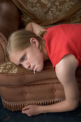 Young girl sitting on the sofa at home watching television with a lollypop in her mouth,
