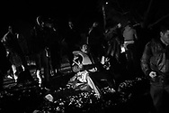 A man, who just landed on the shore, sits for a thankful pray. Refugees from Afghanistan and Syria arrive at night on inflatable boats to the northern shores of Lesbos near Skala Sikaminias, Greece on 05<br /> November, 2015. Lesbos, the Greek vacation island in the Aegean Sea between Turkey and Greece, faces massive refugee flows from the Middle East countries.