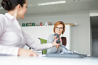 Young businesswoman handing telephone to colleague in office