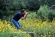 03848-00105 Man watching butterflies at flower gardens at Valley Nature Center Weslaco TX