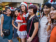 25 DECEMBER 2015 - SINGAPORE, SINGAPORE:   A woman dressed as Santa Claus' assistant poses for photos with shoppers on Orchard Road in Singapore. Orchard Road is the heart of Singapore's upscale shopping and consumerism.   PHOTO BY JACK KURTZ