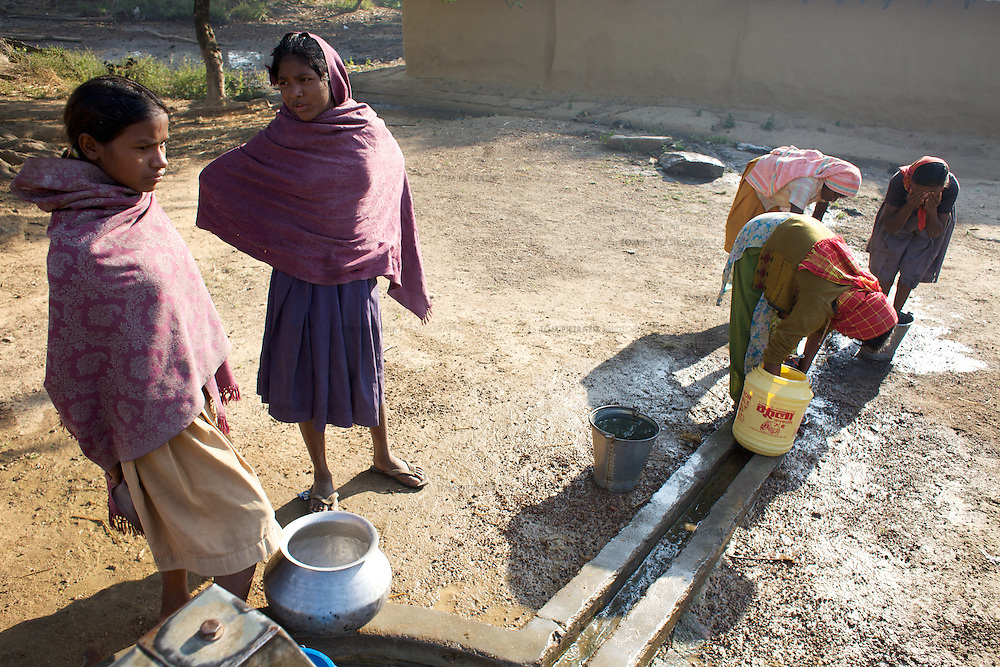 Women and children collect water and bathe at a water pump in the Adivasi (tribal) village of Kanbhita in Ranchi district. UNICEF work to encourage hygiene and good health practices among the women and children of Kanbhita through partners Mahila Samakhya...Mahila Samakhya is UNICEF's partner in eleven districts in Jharkhand. Mahila Samakhya work with Adivasi (tribal) communities in Ranchi district, encouraging good hygiene practices including handwashing and providing practical support for the construction of latrines in an area where two thirds of the population defecate in the open. Mahila Samkhya work with women's self help groups to encourage good waste water management and provide advice on wormi composting. Mahila Samakhya also work in schools and child residential centres, promoting hygiene and sanitation through staff training and the distribution of learning materials. UNICEF are advisors and technical assistants to the Jharkhand government in the implementation of the government's Total Sanitation Campaign (TSC). ..Photo: Tom Pietrasik.Ranchi District, Jharkhand. India.October 28th 2009