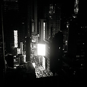 Times Square at electronic billboard at Night.  Hershey's candy signs seen in background.