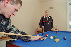 Two male residents of homeless hostel for people with learning difficulties playing game of pool,