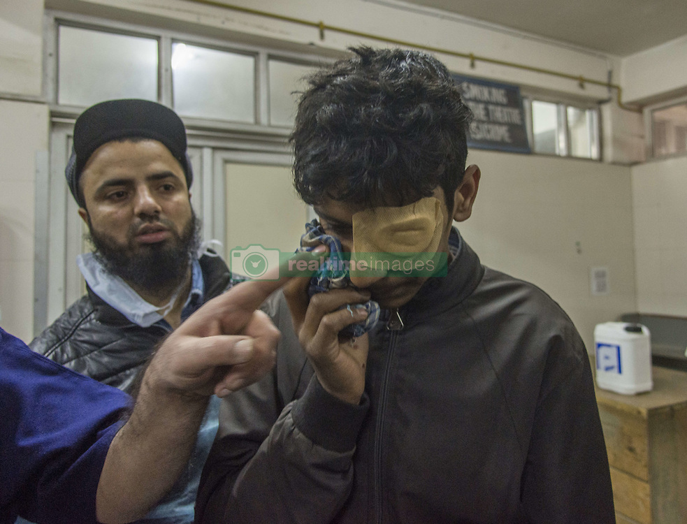 November 20, 2018 - Srinagar, Kashmir, India - Kashmiris help a boy who was blinded in an eye with metal pellets by Indian government forces near the gun battle site, in a hospital  on November 20, 2018 in  Srinagar, the summer capital of Indian administered Kashmir, India. Five people, including an Indian armys paratrooper and four Kashmiri rebels of Hizbul Mujahideen group, Kashmiris largest militant organization, were killed in a brief gunfight between Indian government forces and Kashmiri rebels, in the Nadigam village of south Kashmirs Shopian district on Tuesday. As soon as the  news of gun battle spread among the locals, hundreds of Kashmiri youth marched towards the gun battle site, to support the rebels chanting pro-militant slogans and demanding the end of Indian rule over Kashmir,  which ended up in clashes between Indian government forces and Kashmiri Muslims . Youth hurled rocks and bricks at Indian government forces and the forces in retaliation  used live rounds, metal pellets and teargas shells to stop them from reaching to the gun battle site. Several were wounded in the clashes with bullet injuries including young girls. (Photo by Kabli Yawar/ Nur Photos) (Credit Image: © Kabli Yawar/NurPhoto via ZUMA Press)