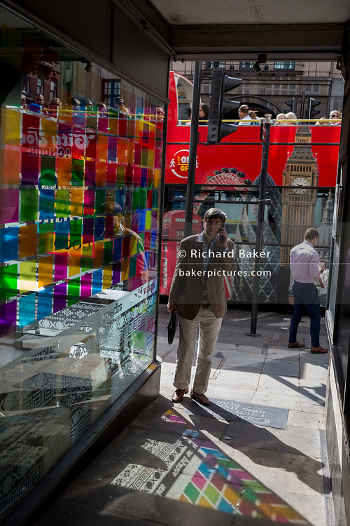 A tour bus drives past coloured light from a corner cafe reflected on the pavement inn Fleet Street in the City of London, the capital's financial district (aka the Square Mile), on 22nd August 2019, in London, England.