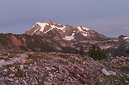 Post sunset light on Mt. Shuksan from the Artist Point to Huntoon Point trail along Kulshan Ridge in Washington State's North Cascades Range. Photographed from Huntoon Point in the Mount Baker Wilderness. Mount Shuksan itself lies in North Cascades National Park.
