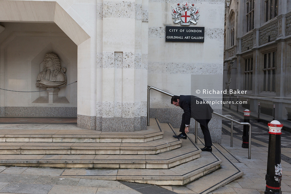 A City businessman bends down to tie a shoelace outside the Guildhall's Art Gallery on 13th February 2017, in the City of London, United Kingdom.