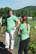 Athens Mayor Steve Patterson talks with Megan Buskirk, environmental strategies coordinator for Athens City-County Health Department, before painting Mile Marker 0 on the HockHocking Adena Bikeway. Buskirk is holding one of four brick patterns volunteers painted on the bikeway. © Ohio University / Photo by Kaitlin Owens