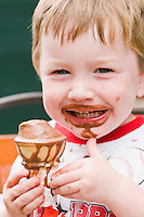 Boy age 3 eating chocolate ice cone cream messy boy child, St. Augustine, Florida, USA