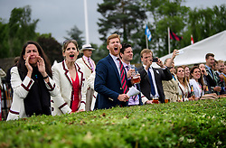 © Licensed to London News Pictures. 28/06/2017. London, UK. Spectators in rowing club colours cheer on a team on day one of the Henley Royal Regatta, set on the River Thames by the town of Henley-on-Thames in England.  Established in 1839, the five day international rowing event, raced over a course of 2,112 meters (1 mile 550 yards), is considered an important part of the English social season. Photo credit: Ben Cawthra/LNP