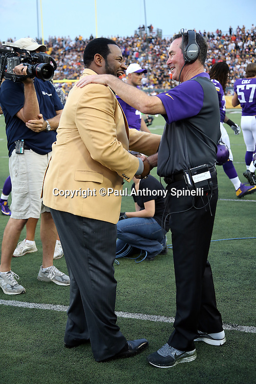 "(L-R) Former Pittsburgh Steelers running back Jerome ""The Bus"" Bettis and recently inducted member of the Pro Football Hall of Fame has a hearty laugh with Minnesota Vikings head coach Mike Zimmer before the 2015 NFL Pro Football Hall of Fame preseason football game against the Pittsburgh Steelers on Sunday, Aug. 9, 2015 in Canton, Ohio. The Vikings won the game 14-3. (©Paul Anthony Spinelli)"