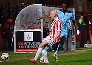 Matt Richards tackles Jordan Slew during the Sky Bet League 2 match between Cheltenham Town and Cambridge United at Whaddon Road, Cheltenham, England on 14 April 2015. Photo by Alan Franklin.
