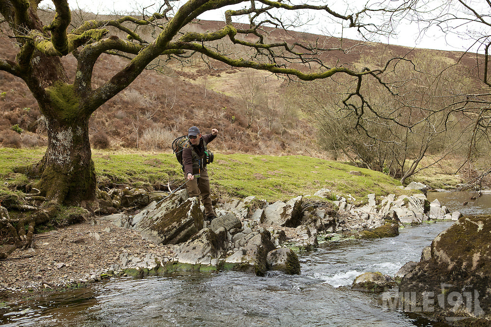 Lewis Hendrie using a bow an arrow cast whilst fly fishing on a river Exmoor.