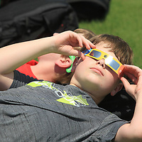 Connor Hankins, 13, an eighth grader at Mooreville Middle School, views the Solar Eclipse through his Eclipse glasses with his classmates on the baseball field Monday afternoon.