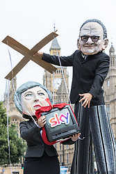 © Licensed to London News Pictures. 29/06/2017. London, UK. Campaigners from Avaaz at a photocall outside Parliament with Rupert Murdoch controlling a puppet Prime Minister Theresa May. Secretary of State for Culture, Media and Sport Karen Bradley will today announce whether Murdoch's takeover bid for Sky has been approved. Photo credit: Rob Pinney/LNP