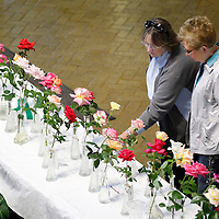 Thomas Wells | BUY at PHOTOS.DJOURNAL.COM<br /> Martha Stancil, left, and Linda Beck both of Mantachie spend a few hours admiring the beauty of the roses submitted for this year's Rose Show at Renasant Bank in downtown Tupelo on Thursday.