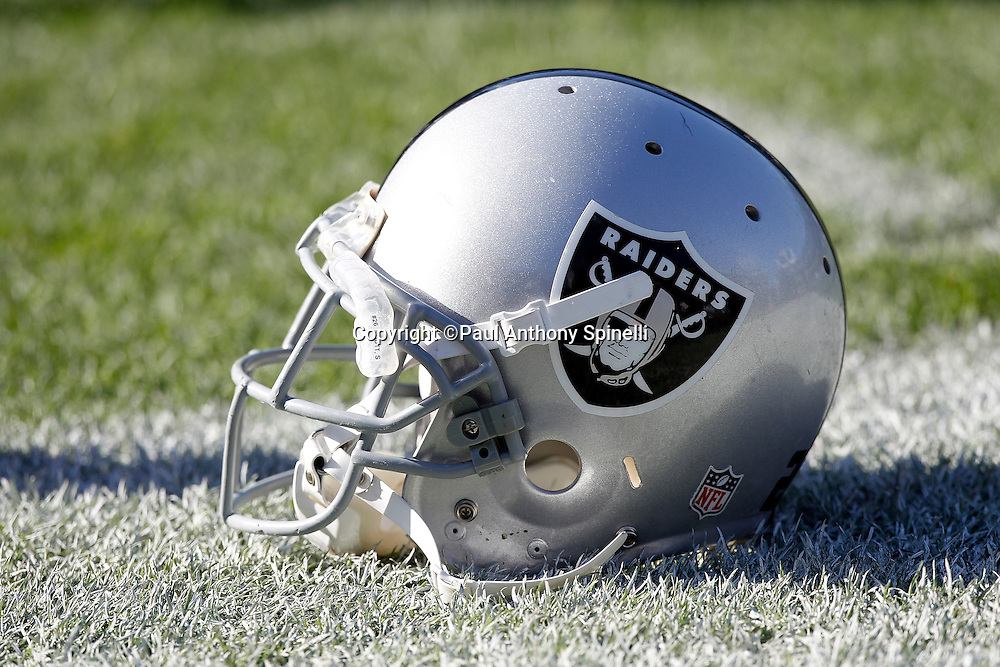An Oakland Raiders helmet lies on the grass during the NFL week 16 football game against the Indianapolis Colts on Sunday, December 26, 2010 in Oakland, California. The Colts won the game 31-26. (©Paul Anthony Spinelli)