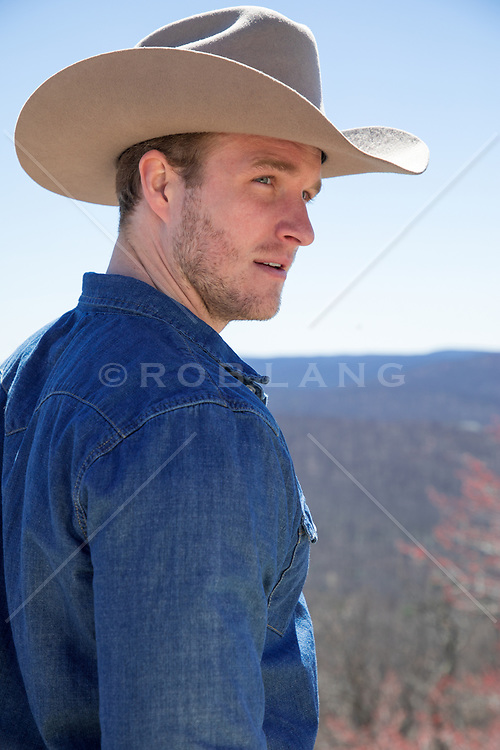 handsome cowboy on a mountain top looking off Portrait of a handsome blonde cowboy with blue eyes outdoors