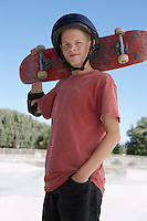Teenage boy (13-15) holding skateboard at skateboard park portrait