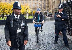 © Licensed to London News Pictures. 28/10/2015. London, UK. Former conservative minister ANDREW MITCHELL MP, riding his bike past police officers on the gate of the Houses Of Parliament on October 28, 2015. Andrew Mitchell was embroiled in a legal battle with Metropolitan police officers following a row at the gates of 10 Downing Street.  Photo credit: Ben Cawthra/LNP