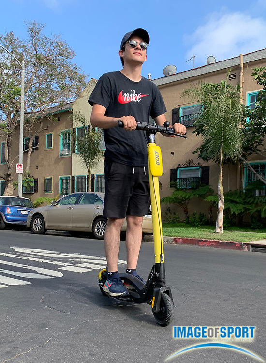 Dylan Stewart of Riverside, Calif., rides a  Bolt electric scooter, Monday, June 24, 2019, in Los Angeles. The yellow scooter features footholds located on either side of the riding board, which the company Bolt Mobility says allows for greater balance. Bolt Mobility, was founded in March 2018 by entrepreneurs Kamyar Kaviani and Sarah Haynes, with brand ambassador Usain Bolt. (Kirby Lee via AP)