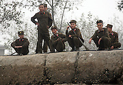 North Korean soldiers socialize on the banks of the Yalu River, on the North Korea-China border in the town of Sunuiju, DPRK October 10, 2006. North Korea declared that it has conducted an underground nuclear test ó becoming only the eighth country to do so.  DPRK, north korea, china, dandong, border, liaoning, democratic, people's, rebiblic, of, korea, nuclear, test, rice, japan, arms, race, weapons, stalinist, communist, kin jong il