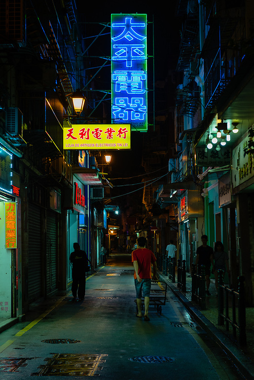 People on street at night in historical district of Macau