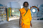 THIMMAMMA MARRIMANU, INDIA - 25th October 2019 - Portrait of Babu Sadhu standing inside the white temple which stands on the mountain opposite the Thimmamma banyan tree in Andhra Pradesh, South India. The site's main entrance is said to be a place where Lord Shiva worshipped and performed penance rituals. Thimmamma Marrimanu is home to the world's largest single tree canopy.