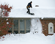 JOHN PETRUNYAK shovels snow off a neighbor's roof in Lancaster, New York on Wednesday, November 19, 2014. Up to six feet of snow fell on the region Tuesday, stranding dozens of motorists on roadways and causing at least six deaths.
