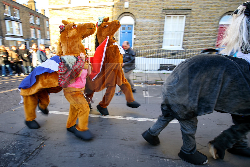 © Licensed to London News Pictures. 11/12/2016. London, UK. The London Pantomime Horse Race takes place in Greenwich, London on Sunday, 11 December 2016. Contenders in pantomime horse costumes take part in comedy race through the streets of Greenwich and use pubs as race checkpoints to raise money for charity. Photo credit: Tolga Akmen/LNP