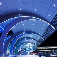 United Arab Emirates, Dubai, Glowing lights outside modern architectural exterior of Dubai International Airport Terminal 3