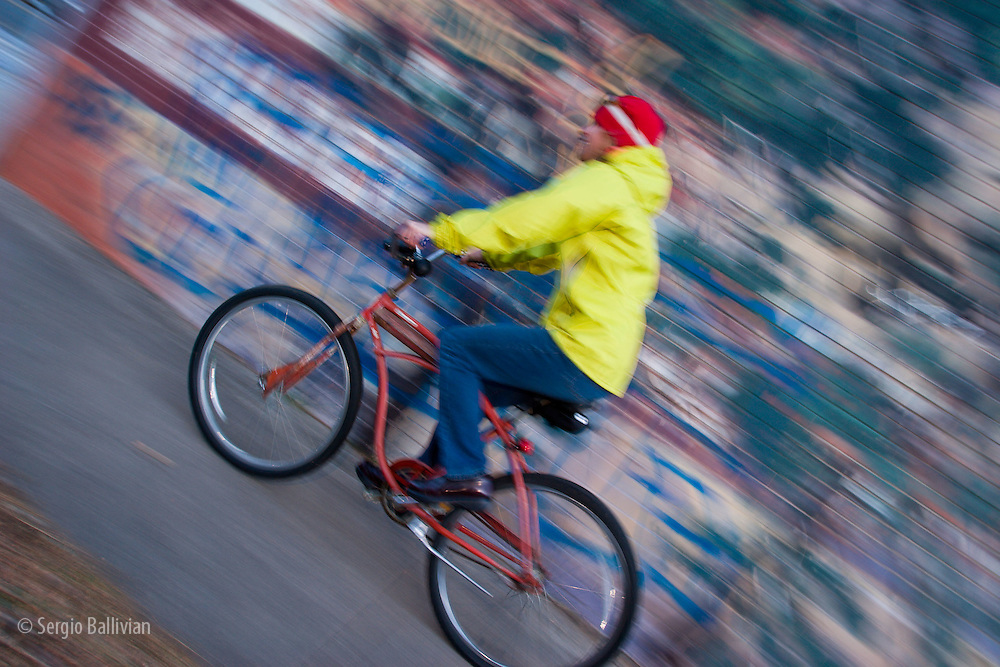 A mid-adult woman rides her cruiser bike along the streets of downtown Boulder, Colorado